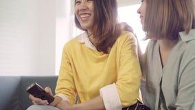 Lesbijska Azjatycka para ogląda TV śmiech w żywym pokoju w domu, słodka para cieszy się śmiesznego moment podczas gdy kłamający n zbiory