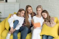 Lesbijska para w przypadkowych ubraniach z ich c?rkami czyta ksi??k? obraz royalty free