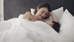 Lesbisch en paar die terwijl thuis het liggen samen in bed koesteren glimlachen Jonge lesbienneskussen en omhelzingen na kielzog  stock videobeelden
