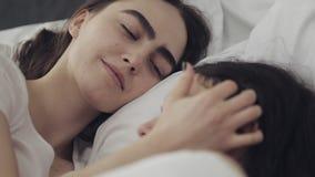Lesbisch en paar die terwijl thuis het liggen samen in bed koesteren glimlachen Jonge lesbienneskussen en omhelzingen na kielzog  stock footage