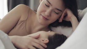 Lesbisch en paar die terwijl thuis het liggen samen in bed koesteren glimlachen Jonge lesbienneskussen en omhelzingen na kielzog  stock video