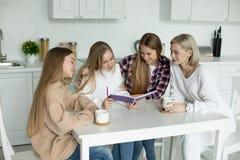 Lesbisch wijfje twee die in vrijetijdskleding thuiswerk controleren hun dochters stock foto's