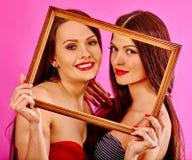 Lesbische Frauen, die Kunstrahmen halten Stockfotos