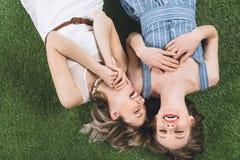 Lesbische lachende Paare beim auf dem Gras zusammen liegen stockfotos