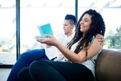Lesbische paar het letten op televisie en het lezen van een boek Royalty-vrije Stock Foto's