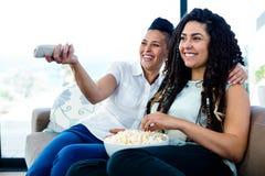 Lesbische paar het letten op televisie met een kom popcorn Royalty-vrije Stock Fotografie