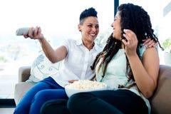 Lesbische paar het letten op televisie met een kom popcorn Stock Foto's