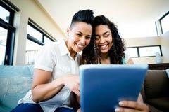 Lesbische paarzitting op bank en het gebruiken van digitale tablet Stock Foto
