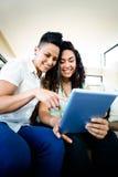 Lesbische paarzitting op bank en het gebruiken van digitale tablet Royalty-vrije Stock Foto's
