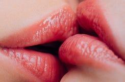 Lesbischer KUSS Sinnliches nass weibliches Lippenküssen Lesbische Vergnügen Reizvolles M?dchen sitzt Paarmädchen, die nah Lippen  lizenzfreies stockfoto
