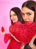 Lesbiska kvinnor som rymmer hjärtasymbol royaltyfria foton