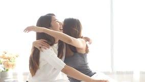 Lesbiska lyckliga par för asiatiska kvinnor som vaknar upp i morgon Asiatiska flickor som sitter på säng som hemma sträcker i hem lager videofilmer