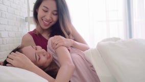 Lesbiska lyckliga par för unga asiatiska kvinnor som hemma vaknar upp i morgonen på säng i sovrum stock video