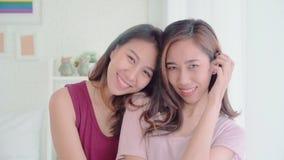Lesbiska lyckliga par för unga asiatiska kvinnor som ler och ser till kamerastund för att koppla av i hennes sovrum hemma arkivfilmer