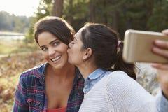 Lesbiska par i bygden kysser och tar en selfie arkivfoton