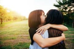 Lesbiska par omfamnad tillsammans förälskad förhållandenedgång Två asiatiska kvinnor som har gyckel på, parkerar tillsammans Royaltyfria Foton