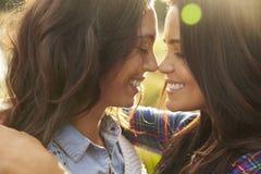 Lesbiska par omfamnar rörande näsor, stängda ögon, nära övre royaltyfria foton