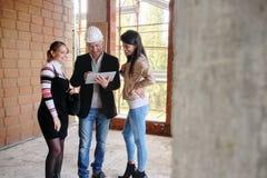 Lesbiska par som köper det nya hemmet och talar till affärsmannen royaltyfri bild