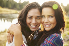Lesbiska par som kramar vid en sjö, ser till kameran, slut upp arkivbilder