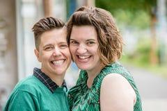 Lesbiska par som trycker på kinder Fotografering för Bildbyråer