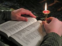 Lesebibel durch Kerzenlicht lizenzfreie stockfotos