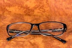 Lesebrille auf einem braunen Hintergrund Stockbild