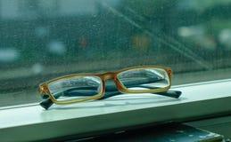 Lesebrille auf Zugfenster lizenzfreie stockbilder