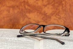 Lesebrille ist auf einem offenen Buch Lizenzfreie Stockfotos