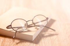 Lesebrille mit Büchern auf hölzerner Tabelle, Weinleseart Stockbilder