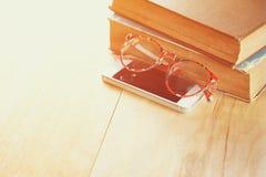 Lesebrille, Stapel alte Bücher und intelligentes Telefon über Holztisch, Retro- gefiltertes Bild Stockfotos