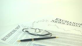 Lesebrille und Stift sind auf den Nachrichtenmedien stockbilder