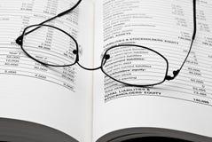Lesegläser auf geöffnetem Geschäftsbuch Stockbilder