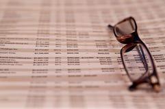 Lesegläser oben auf Finanzpapier Stockbilder