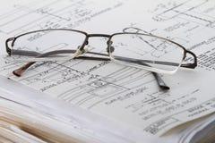 Lesegläser und Arbeits-Papiere Stockfotos