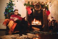 Lesekerl auf dem Hintergrund des Weihnachtsbaums und des Kamins stockfotos