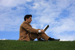 Lesen auf dem Gras lizenzfreie stockfotografie