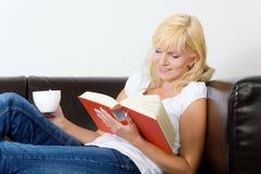 Lesen auf dem Sofa Stockbild