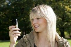 Lesen der jungen Frau sms Stockfotos