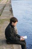 Lesen durch den Fluss Stockbild