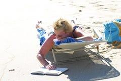 Lesen an einem heißen Strand-Tag stockfotografie