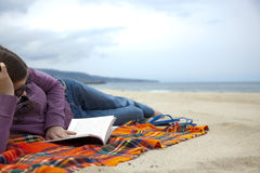 Lesen eines Buches auf dem Strand stockbilder