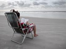 Lesen eines Buches im Strand Stockbild