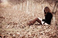 Lesen eines Buches im Wald Stockfotografie