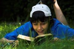 Lesen im Gras Stockfotografie