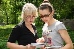 Lesen mit zwei junges Kursteilnehmern Stockbilder