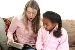 Lesen mit zwei Mädchen Stockbilder