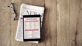 Lesenachrichten auf Tablette und Zeitung auf hölzernem Hintergrund lizenzfreie stockfotos