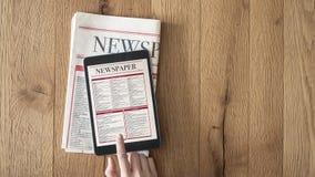 Lesenachrichten auf Tablette und Zeitung auf hölzernem Hintergrund stockfotos