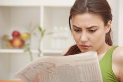 Lesende falsche Nachrichten der Frau in der Zeitung Lizenzfreies Stockbild