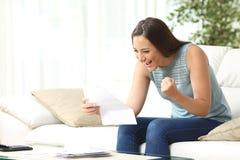 Lesende gute Nachrichten der aufgeregten Frau im Buchstaben Stockfotografie